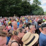 A solemn crowd realise that bloke is not gonna sit down.  And Froome has sat up, and so has Wiggo..